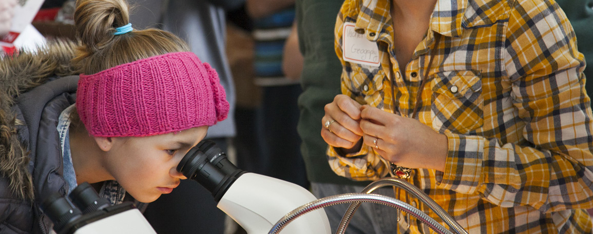 A girl peers through a microscope during one of University of Utah's 2014 Science Day's workshops.