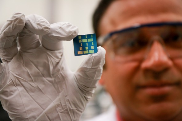 University of Utah materials science and engineering associate professor Ashutosh Tiwari holds up a substrate layered with a newly discovered 2D material made of tin and oxygen. Tiwari and his team have discovered this new material, tin monoxide, which allows electrical charges to move through it much faster than common 3D material such as silicon. This breakthrough in semiconductor material could lead to much faster computers and mobile devices such as smartphones that also run on less power and with less heat.