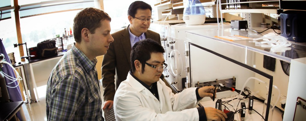 Ben Bunes (left), Ling Zang and Chen Wang (in lab coat), all researchers from the University of Utah's material sciences and engineering department, demonstrate a new prototype detector that can sense explosive materials and toxic gases. The research team developed a new material for the detector that can sense alkane fuel, a key ingredient in such combustibles as gasoline, airplane fuel and homemade bombs.