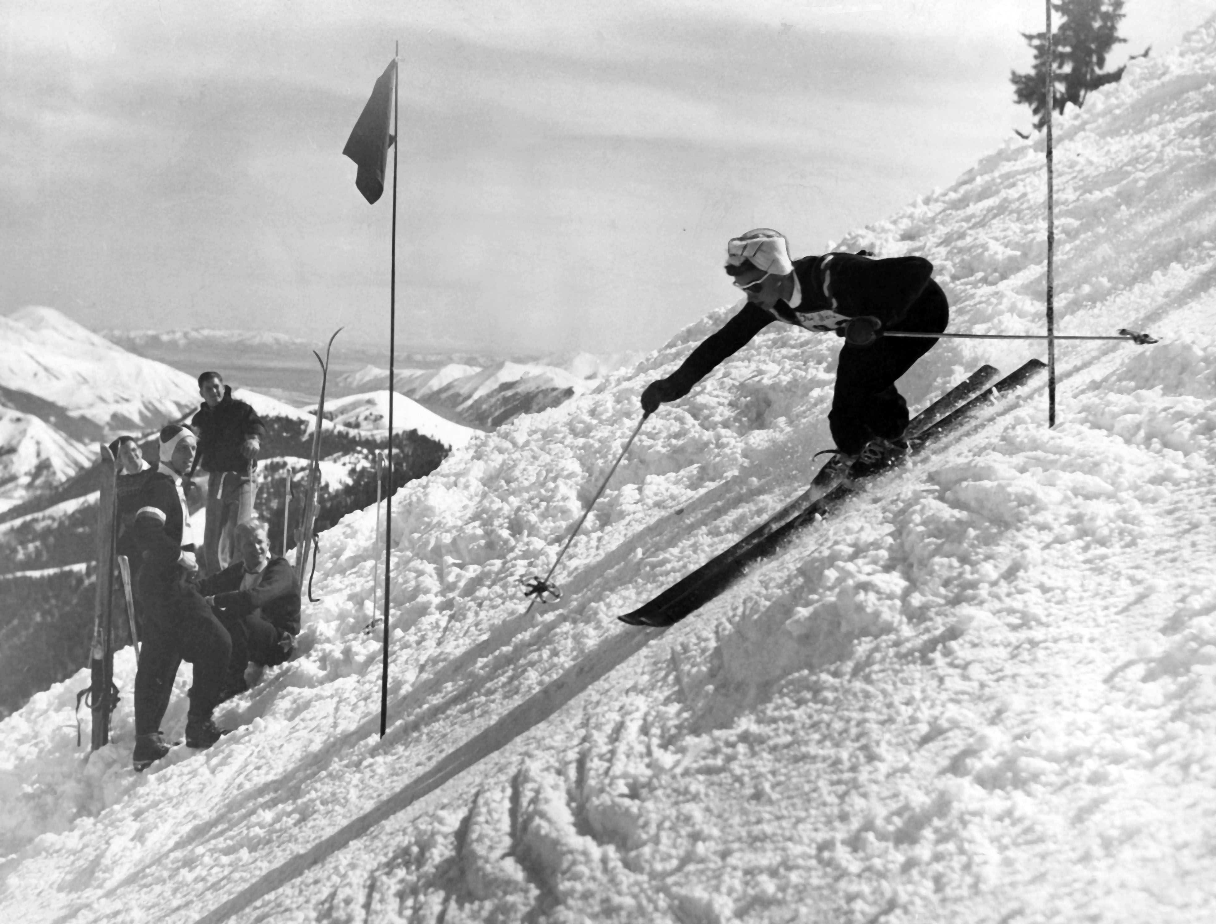 A woman racing around a flag, while others watching, race course at a Utah ski resort, 1940s-1950s; Suzy Rytting Collection